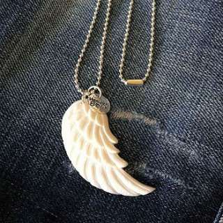 This is a beautiful hand carved bone angel wing pendant sitting on a